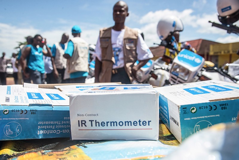 Boxed Infrared thermometers on a table ready to be distributed. UNICEF and UN members stand in the background ready to deploy.