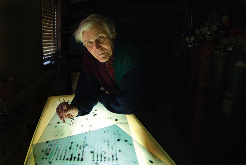Carl Woese, a white man with grey hair and holding a pair of glasses, looks up towards the camera from a lightbox.