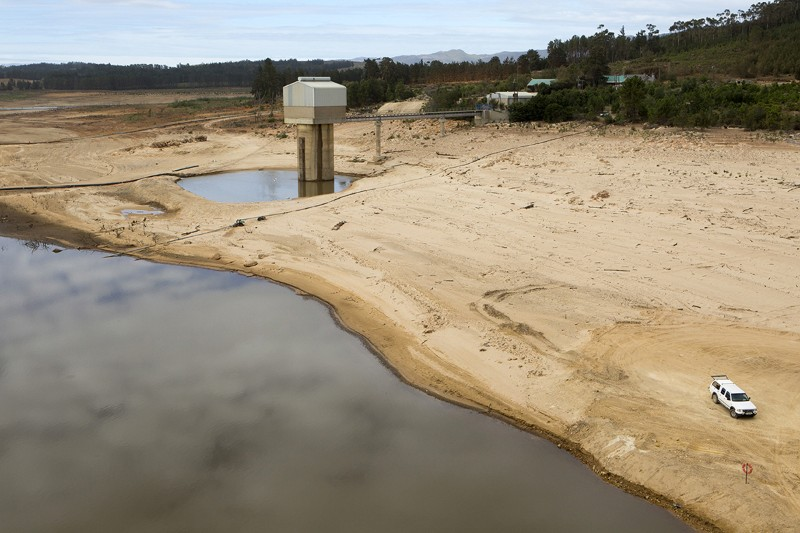 Low levels of water in Theewaterskloof Dam and Reservoir, with a car parked on the dried out bed.