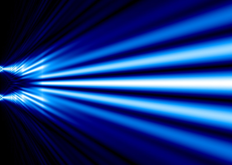 Blue light splitting into wave like interference pattern during a double slit experiment.