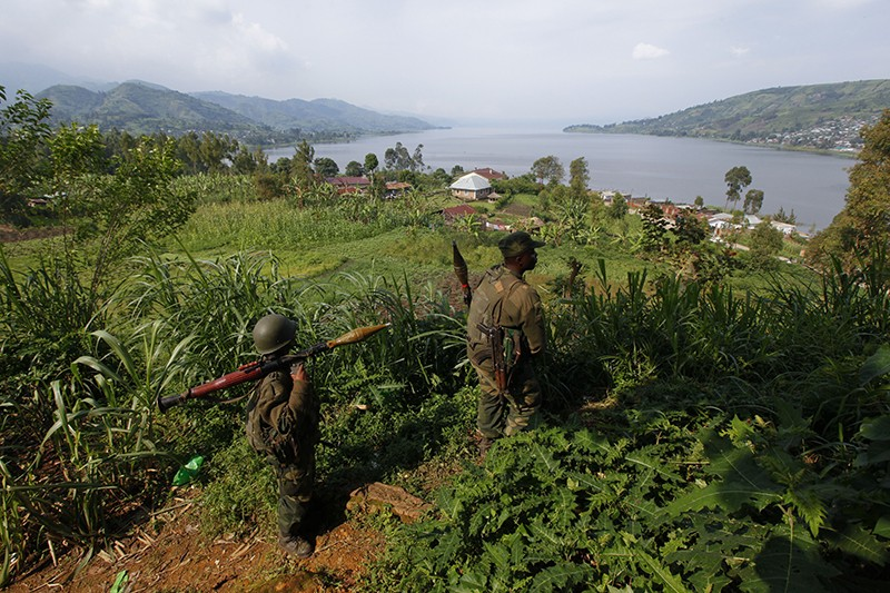 Two Congolese Government troops reach the top of a green hill overlooking Lake Kivu. Buildings can be seen by the lake shore