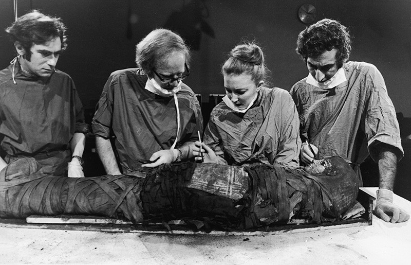 L-R - Drs Frank Leek, Edmund Tapp, Rosalie David and Ahmed examine a mummy on an operating table. David holds a poised scalpel