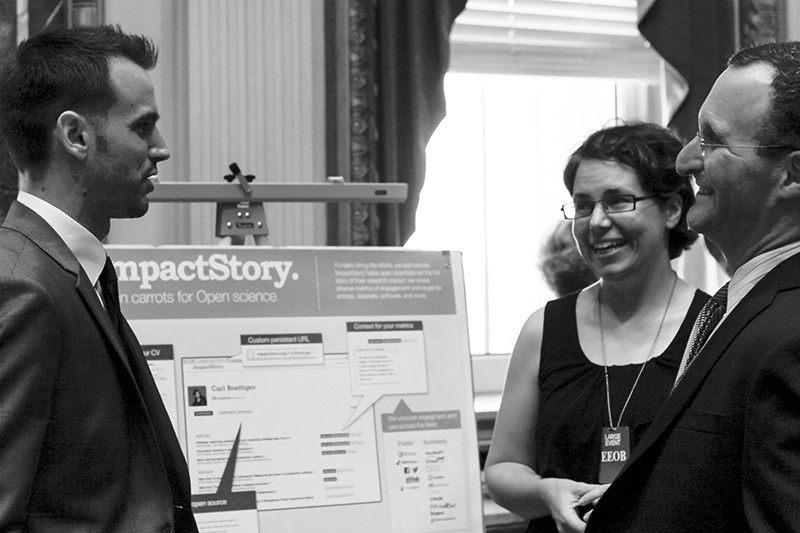 B+W photo of Priem (L) and Piwowar (c) talking to Rossner (r) in front of an ImpactStory presentation board at the White House