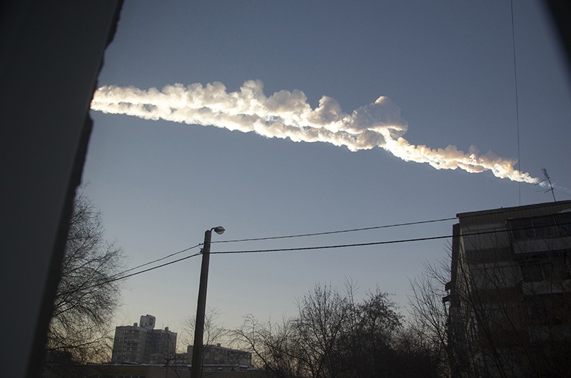 A billowing contrail across a blue sky, seen in between two buildings in Russia.