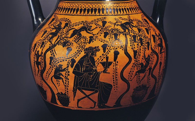 Close up photograph of an orange 6th century Greek vase, decorated with a black relief of a man drinking in a vineyard