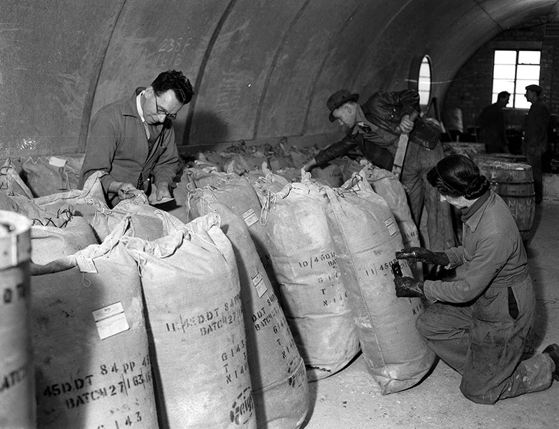 Three people pack raw DDT into sacks in a hangar/bunker.