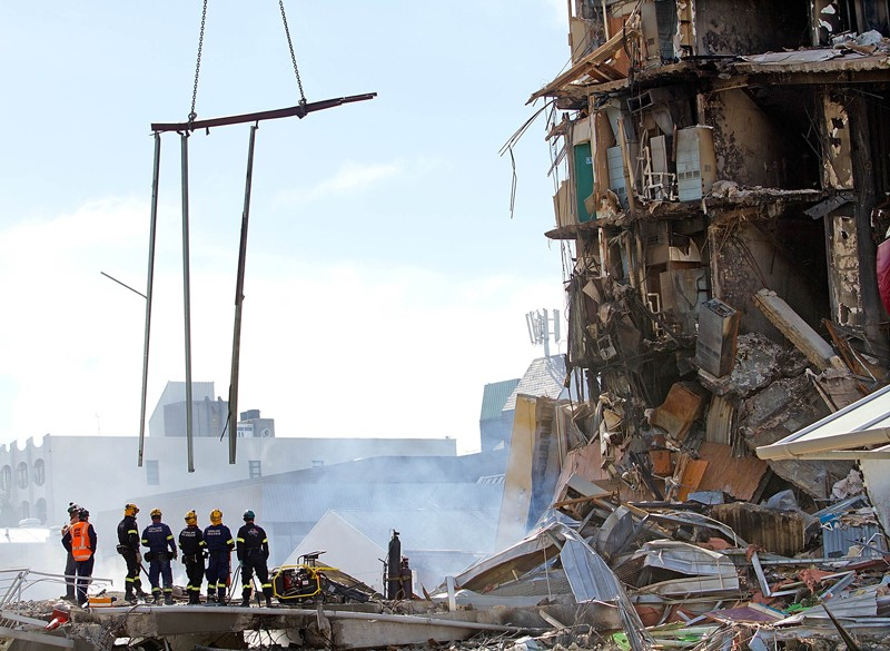 Rescuers stand among the ruins of building destroyed by the 2011 Christchurch earthquake