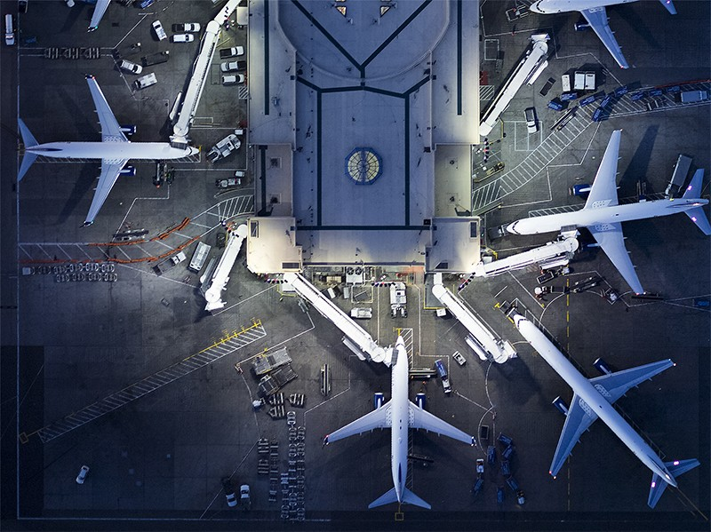 Aerial view of airliners, staff, vehicles, ramps, gates and the Control Tower at LAX airport lit up at night.