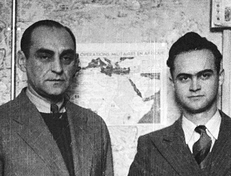 Antoni Palluth (left) and his cousin Sylwester Palluth stand in front of a chart of North African military operations