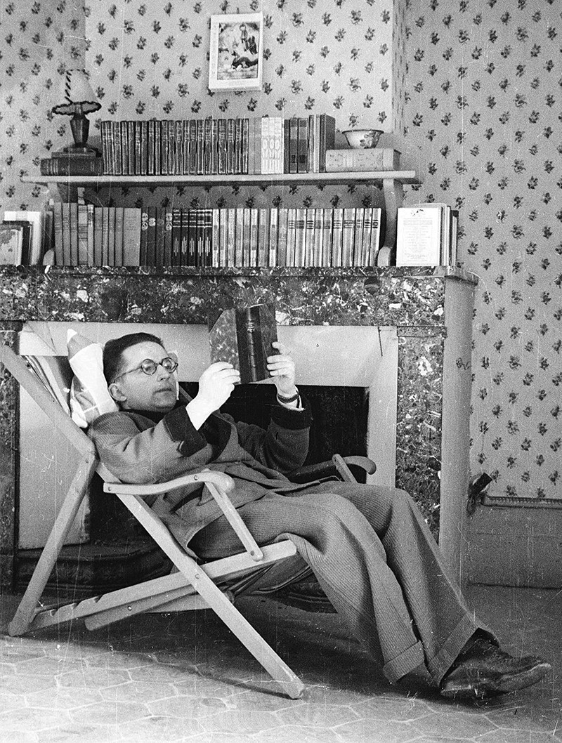 Marian Rejewski reclines in a deck chair reading a book in front of a fireplace