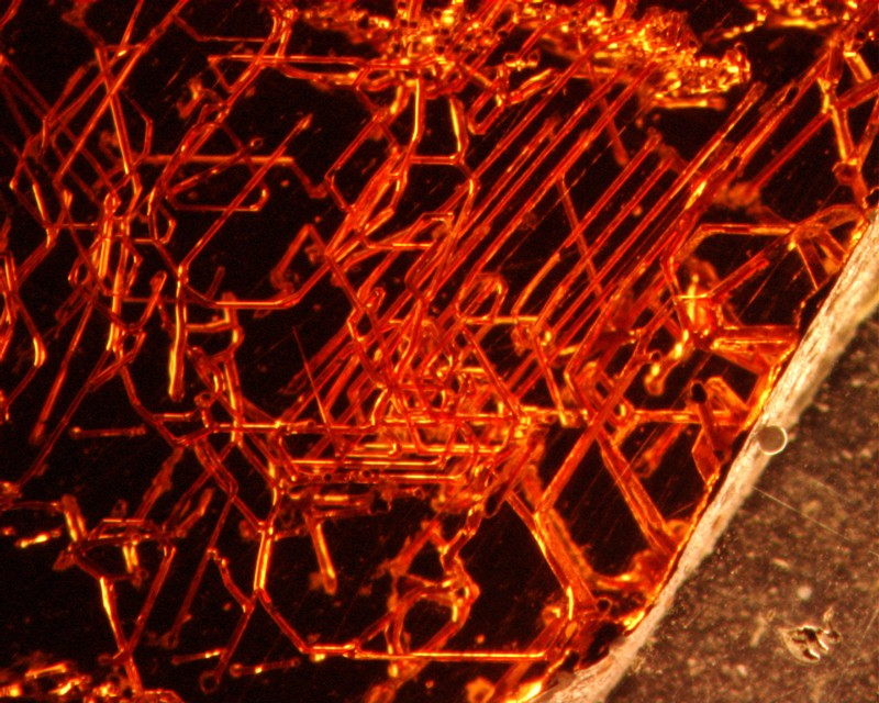 Microscopic tubular structures in red garnet