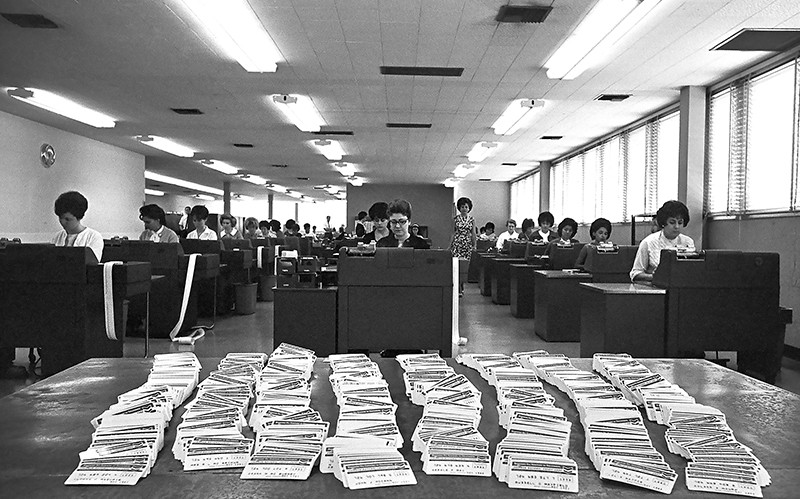 Rows of mostly women working in a Standard Oil office. A stack of Standard Oil credit cards sit on the table at front