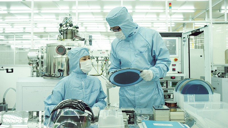 two researchers looking at silicon device in clean room at DGIST