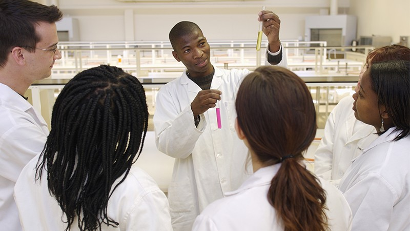 photo of scientist and students in laboratory