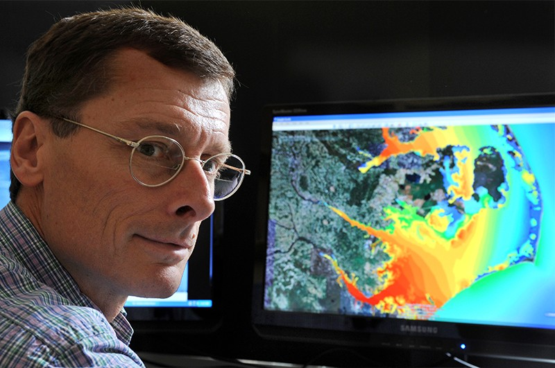Dr Richard Luettich. BEhind him a screen is shown with a computer mdel for predicting storm surges.