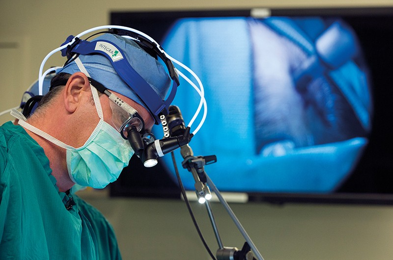 Neurosurgeon John Sampson places a treatment-infusing catheter into the brain of a patient