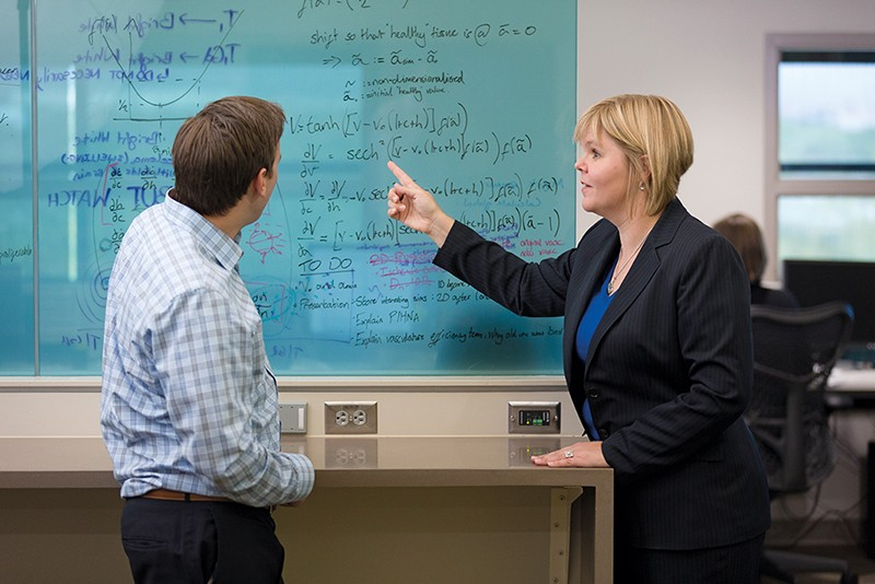 Kristin Swanson stands in front of a whiteboard with a colleague
