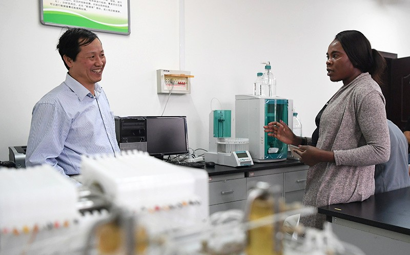 A Namibian agricultural technology officer (R) learns about combating desertification from a scientist (L) in a lab in Lanzhou.