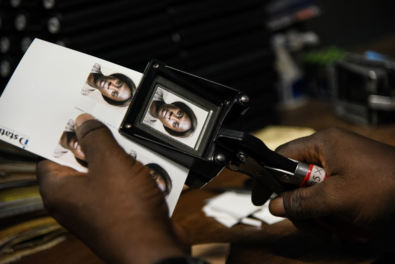 A man cuts passport photos of a woman at a photography studio in Mali