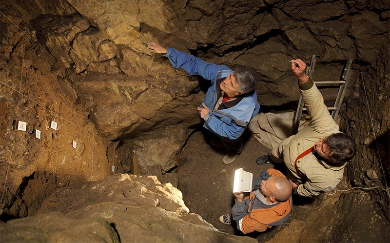 Roberts, Ulianov and Kozlikin (clockwise from top) point and take notes underground in East Chamber of Denisova Cave