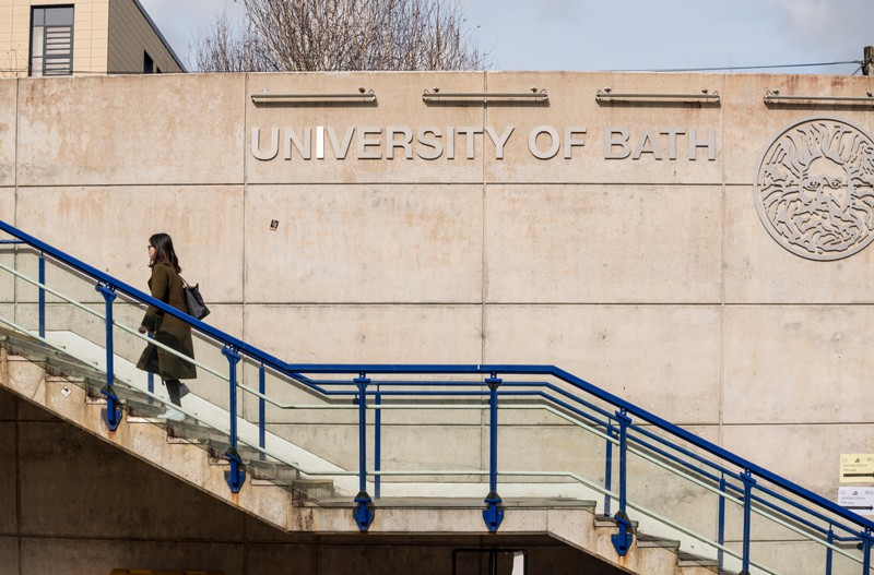 A student walking up stairs, University of Bath
