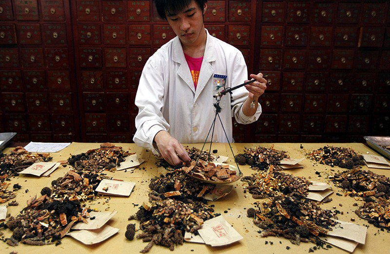 A traditional-medicine pharmacist stands behind a desk covered in dried product