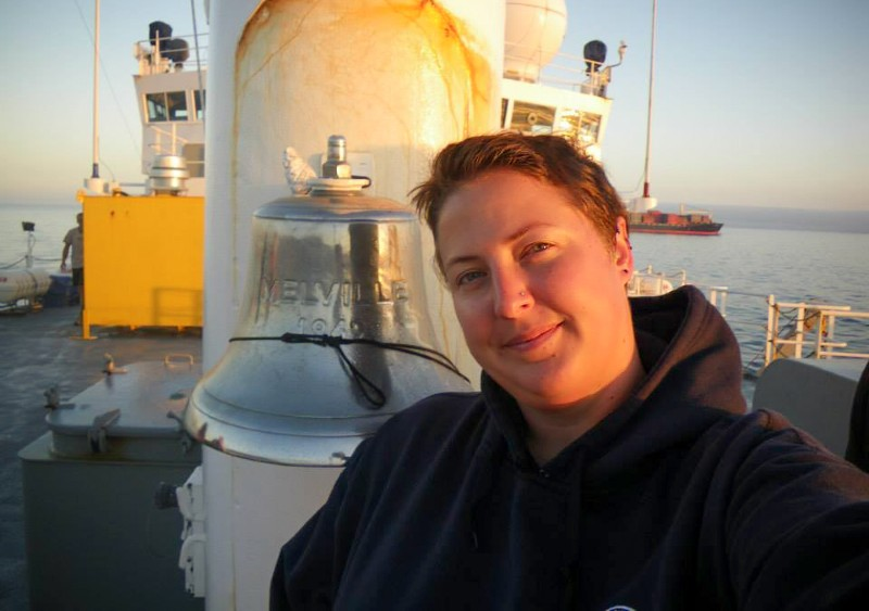 Melissa MIller poses by a ship's bell