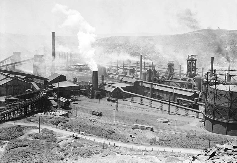 Black and white photo of Bethlehem Steel Mill in Johnstown, PA, from a hill. Smoke rises from the stacks