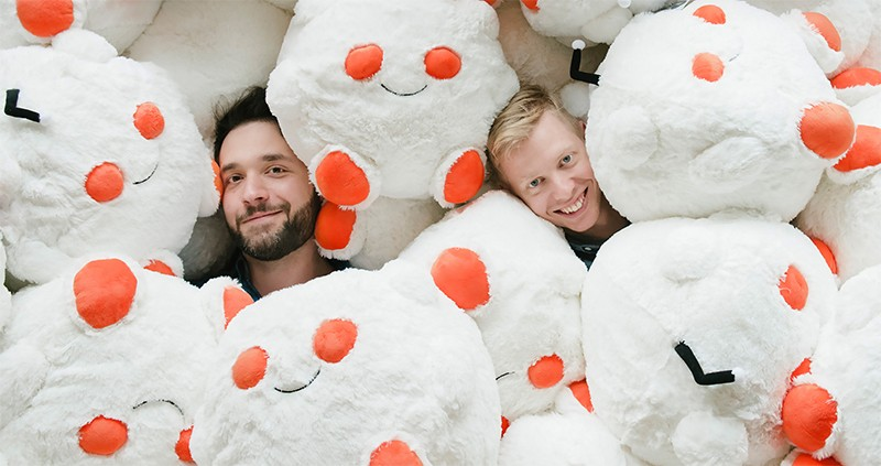 Ohanian (l) and Huffman (r) smile up from under a pile of Reddit-logo-shaped soft toys