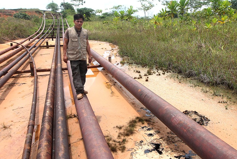 Segundo Cariajano stands on a large oil pipe running over a muddy oozing lake bed full of oil.