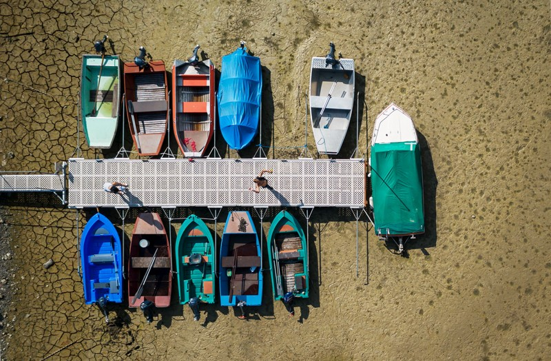 Boats beside a jetty on the dried out lake bed
