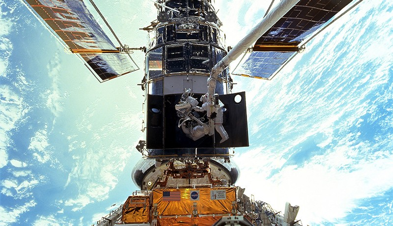 Two astronauts replace gyroscopes on the Hubble telescope during an EVA in 1999. The Earth looms brightly below them.