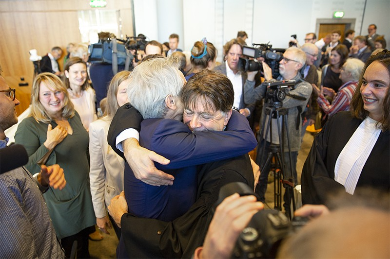 A campaigner and a lawyer hug as they and other campaigners celebrate the court's ruling at the Hague