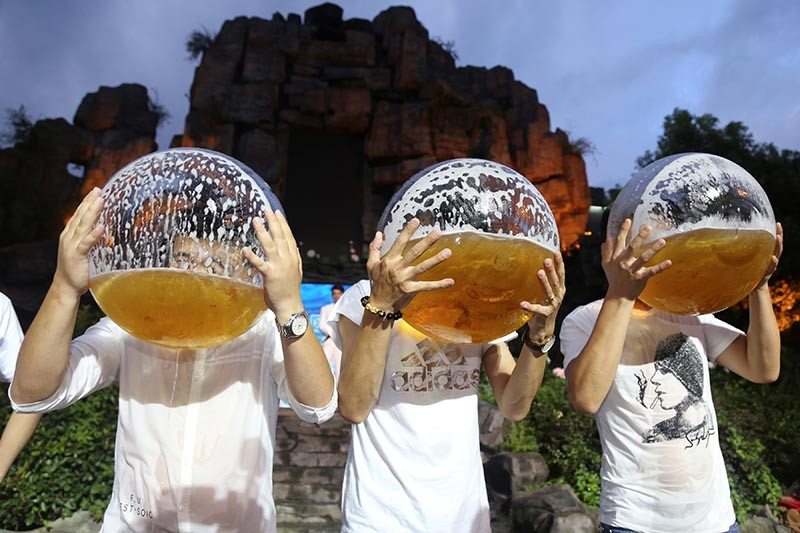 People drink beer from fish bowls at a beer drinking competition in China