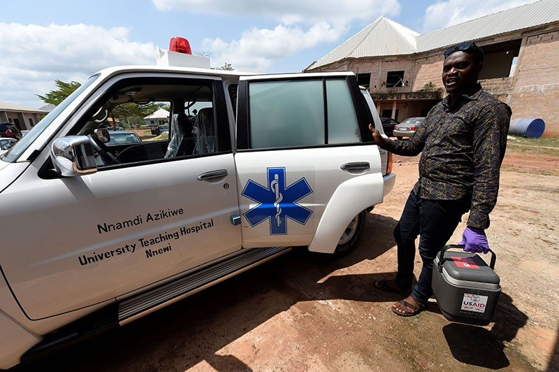 A health worker arrives with a cooler containing blood samples for testing at the Institute of Lassa Fever Research and Control
