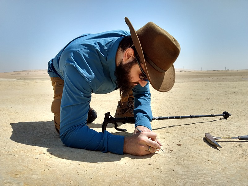 Carlos Peredo wearing a brimmed hat excavates fossils on a desert plane.