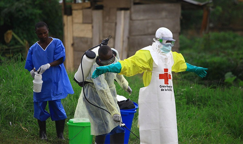 A health worker sprays disinfectant on his colleague after working at an Ebola treatment center in Beni, Eastern Congo