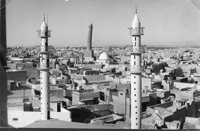 Black and white photo showing three tall minarets and houses in Mosul. The centre minaret is leaning.