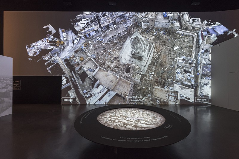 A low table at front showing an aerial view of a city. In the background a large screen shows virtual constructions amid rubble