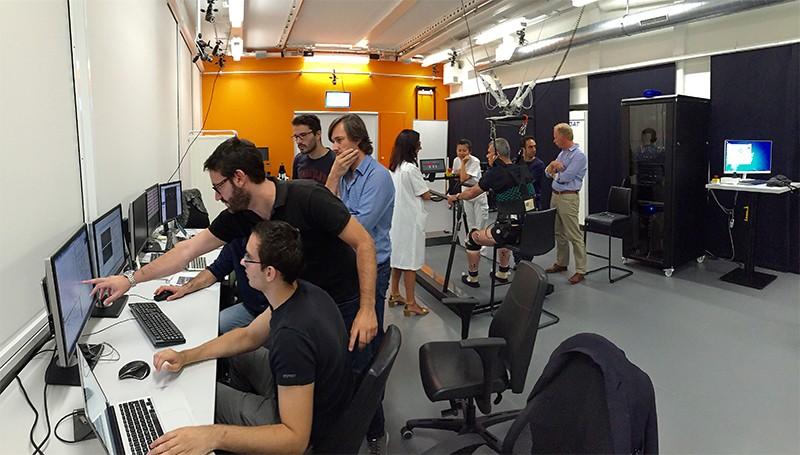 Vista de la plataforma experimental.  Los investigadores observan los datos en las pantallas de la izquierda, un paciente está en el aparejo de la derecha