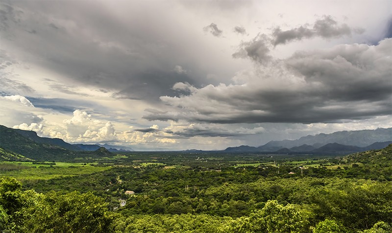 View of Theni Valley under a cloudy sky, with the Western Ghats and Megamalai in the distance