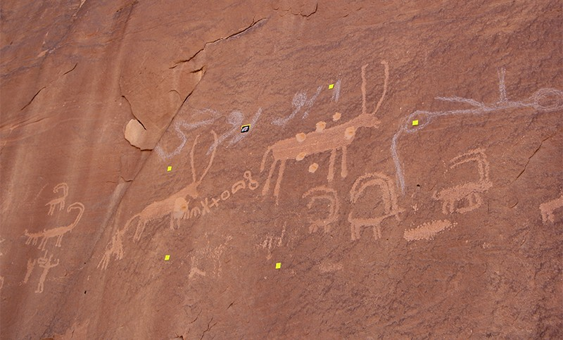 Rock paintings of antelope like animals and symbols scattered with bullet holes + damage