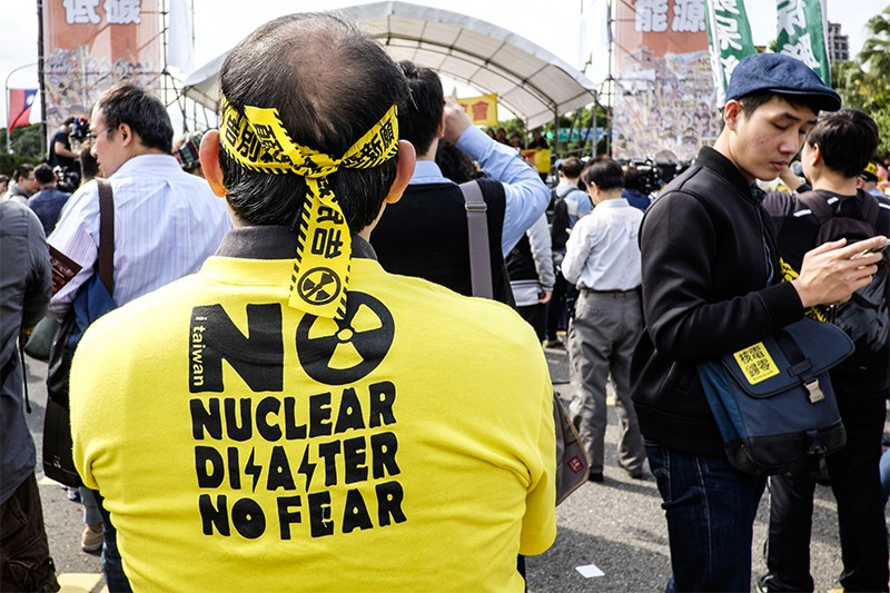 A man in a 'No nuclear no fear' tshirt and with a bandana made from warning tape stands with his back to the camera.