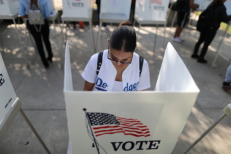 Cynthia Lazo, 25, votes in an outdoor booth during midterm elections on Oct 24th 2018