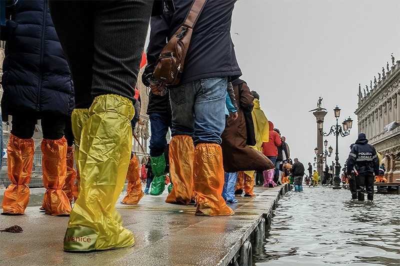 Tourists in colourful waterproofs walk across an emergency wooden boardwalk in St. Mark's Square in Venice to avoid floodwater