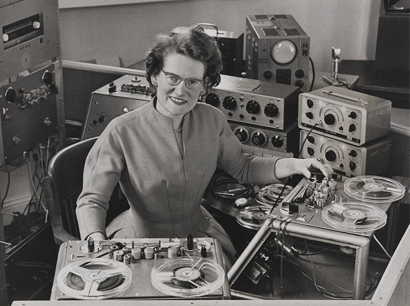 Daphne Oram smiles in her Kent studio surrounded by tape machines, mixers and electronic equipment.