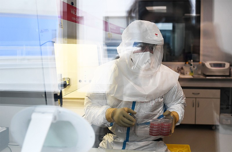 A scientist in a hazmat suit works with Koch's bacillus in a biomedical laboratory, seen through a glass window.