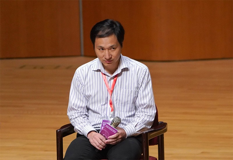 He Jiankui, seated, looks up as he answers questions during his presentation at the human genome editing summit on 28th November
