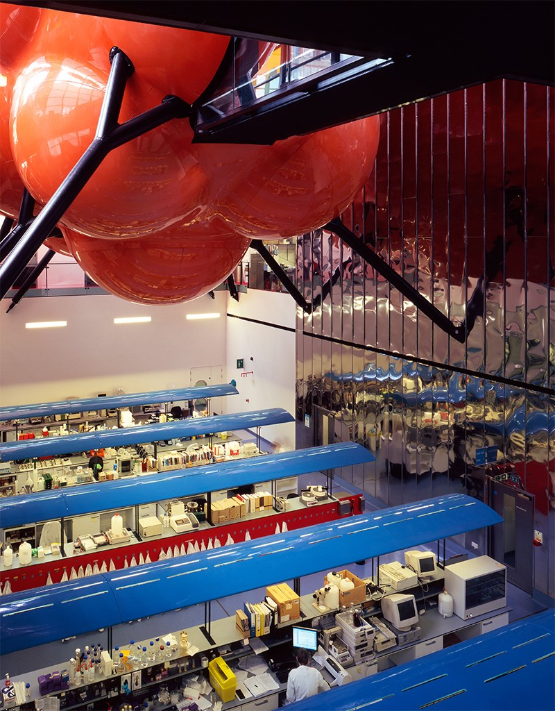 View of the Blizard building with suspended red meeting room structure at top ad colourful open plan lab benches at ground level