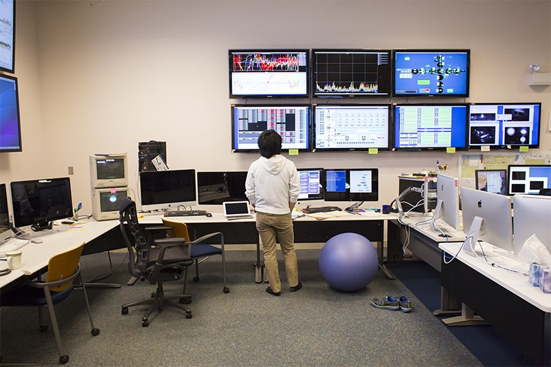 A scientist looks at screens showing LIGO data in a control room.